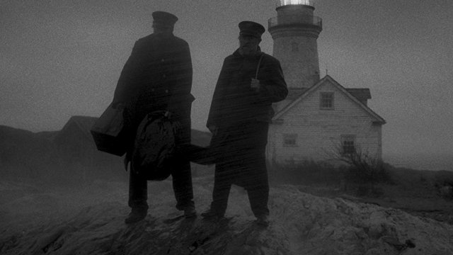 Two silouhetted men stand in front of a lighthouse at night