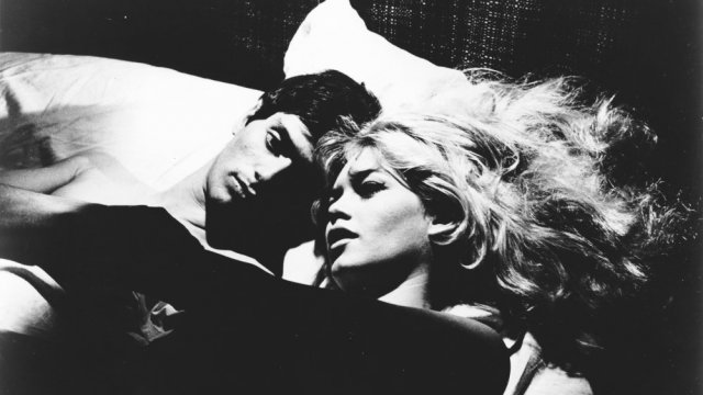 couple lying in bed he has short black hair and she has long blond hair