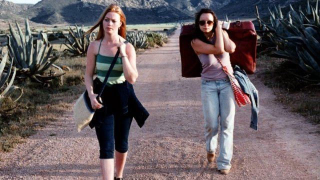2 women walking on a deserted road carrying a suitcase